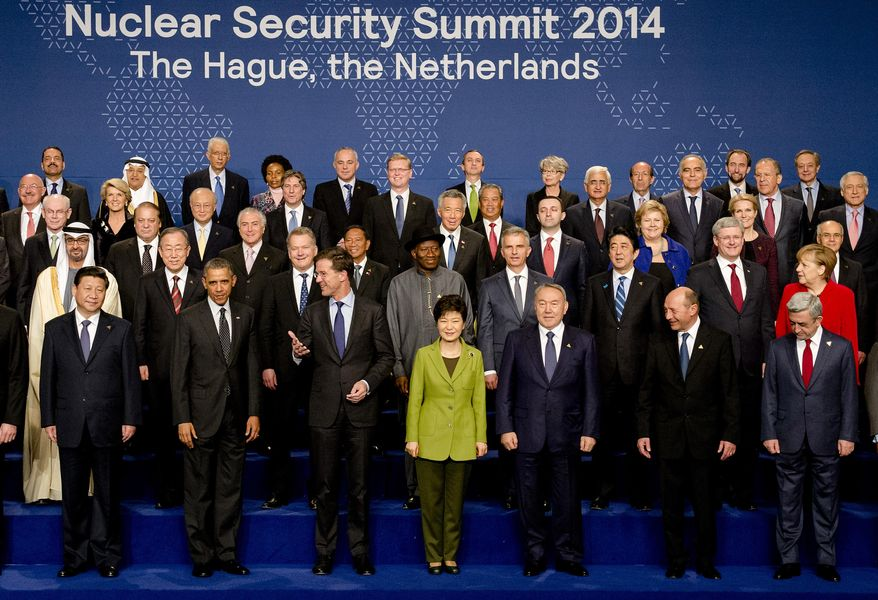 Russia's Foreign Minister Sergey Lavrov, third from top right corner, watches as U.S. President Barack Obama, second left front row, and Dutch Prime Minister Mark Rutte, gesturing, talk when posing for a family photo on the last day of the Nuclear Security Summit (NSS) in The Hague, Netherlands, Tuesday, March 25, 2014. (AP Photo/Robin van Lonkhuijsen, POOL)