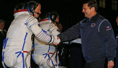Oleg Ostapenko, right, head of the Russian Federal Space Agency, or Roscosmos, shakes hands with U.S. astronaut Steven, left, a crew member of the mission to the International Space Station (ISS) prior the launch of a Soyuz-FG rocket at the Russian leased Baikonur cosmodrome, Kazakhstan, Wednesday, March 26, 2014. (AP Photo/Dmitry Lovetsky, Pool)