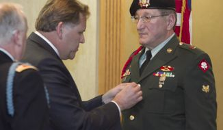 U.S. Congressman Mike Rogers pins the Bronze Star Medal with Valor on PFC Andrew Kach, who served in the Vietnam war, in a ceremony at the American Spirit Centre, Monday, March 17, 2014. (AP Photo/Livingston County Daily Press & Argus, Gillis Benedict)