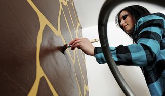 In this March 11, 2014 photo, artist Miranda Munns paints giraffe spots on the wall of her client Taylor Mayer's future son's nursery in Mayer's Somonauk, Ill. home. Munns, a Plano, Ill., resident who graduated from Northern Illinois University in 2012 with a Bachelor of Fine Arts in painting, said she is struggling to find an art-related job while working her full-time job at a gas station. (AP Photo/Daily Chronicle, Danielle Guerra)  MANDATORY CREDIT
