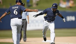 Milwaukee Brewers' Khris Davis, right, celebrates his home run against the San Francisco Giants with third base coach Ed Sedar (6) during the fifth inning of a spring exhibition baseball game, Tuesday, March 25, 2014, in Phoenix. (AP Photo/Ross D. Franklin)