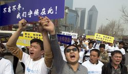 """Chinese relatives of passengers onboard the missing Malaysia Airlines plane, flight MH370, shout in protest as they march towards the Malaysia embassy in Beijing, China, Tuesday, March 25, 2014. Furious over Malaysia's handling of the lost jetliner a day after the country said the passengers must be dead, Chinese relatives of the missing marched Tuesday to the Malaysia Embassy, where they threw plastic water bottles, tried to rush the gate and chanted, """"Liars!"""" The blue placard reads: """"We won't leave or ditch you, we will wait right here.""""(AP Photo/Ng Han Guan)"""