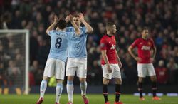 Manchester City's Edin Dzeko, second left, celebrates with teammates Samir Nasri after scoring against Manchester United during their English Premier League soccer match at Old Trafford Stadium, Manchester, England, Tuesday March 25, 2014. (AP Photo/Jon Super)