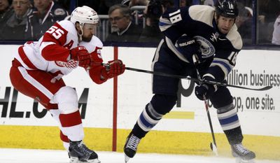 Columbus Blue Jackets' R.J. Umberger , right, passes the puck in front of Detroit Red Wings' Niklas Kronwall, of Sweden, in the first period of an NHL hockey game in Columbus, Ohio, Tuesday, March 25, 2014. (AP Photo/Paul Vernon)