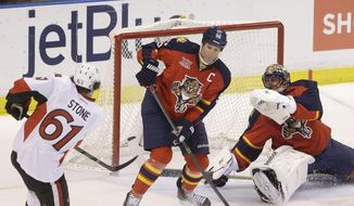 Ottawa Senators right wing Mark Stone (61) scores a goal against Florida Panthers defenseman Ed Jovanovski (55) and goalie Roberto Luongo (1) during the second period of an NHL hockey game, Tuesday, March 25, 2014 in Sunrise, Fla. (AP Photo/Wilfredo Lee)