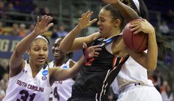 Oregon State forward Deven Hunter (32) is fouled as South Carolina's Asia Dozier (31) goes for the ball during the first half of a second-round game of the NCAA women's college basketball tournament, Tuesday, March 25, 2014, in Seattle. (AP Photo/The Oregonian, Randy L Rasmussen) MAGS OUT, TV OUT, LOCAL TV AND INTERNET OUT, (THE MERCURY, WILLAMETTE WEEK, PAMPLIN MEDIA GROUP OUT)