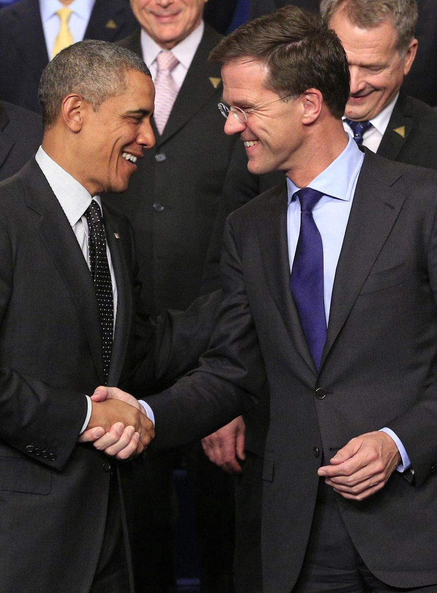 U.S. President Barack Obama, left, shakes hands with Dutch Prime Minister Mark Rutte, right, as they pose for a group photo on the last day of the Nuclear Security Summit (NSS) in The Hague, Netherlands, Tuesday, March 25, 2014. (AP Photo/Yves Logghe)