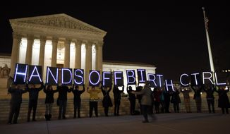 "A group of people organized by the NYC Light Brigade and the women's rights group UltraViolet, use letters in lights to spell out their opinion, in front of the Supreme Court, Monday, March 24, 2014, in Washington. Holding the ""H"" in ""Hands"" is Rep. Keith Ellison, D-Minn. The Supreme Court is weighing whether corporations have religious rights that exempt them from part of the new health care law that requires coverage of birth control for employees at no extra charge. (AP Photo/Alex Brandon)"