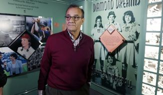 Former New York Yankees manager Joe Torre tours an exhibit on women in baseball during his orientation visit at the Baseball Hall of Fame on Tuesday, March 25, 2014, in Cooperstown, N.Y. Torre will be inducted to the hall in July. (AP Photo/Mike Groll)