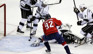 Washington Capitals center Evgeny Kuznetsov (92), from Russia, watches his goal to tie get past Los Angeles Kings goalie Jonathan Quick (32) and center Anze Kopitar (11), from Slovenia, in the third period of an NHL hockey game, Tuesday, March 25, 2014, in Washington. The Kings won 5-4 in a shootout. (AP Photo/Alex Brandon)