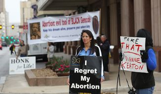 ** FILE ** In this photo taken on Monday, March 24, 2014, anti-abortionist advocates Cynthia Serna, left, and Rosanne Keinath gather with others as they protest outside a Planned Parenthood fundraiser luncheon, where actress Diane Keaton was the featured speaker, at the Marriott Rivercenter Hotel in San Antonio. (AP Photo/The San Antonio Express-News, Jerry Lara)