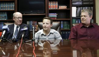 "Lucas McConnell, 13, center, speaks during a news conference with his attorney Todd Clement, left, and his father Kevin McConnell by his side Wednesday, March 26, 2014, in Burleson, Texas.  The family of Lucas McConnell, injured by a drunken teen driver whose attorneys later claimed he suffered from ""affluenza,"" plans to continue its lawsuit against the driver. While most families who sued Ethan Couch over a wreck that left four dead have settled, the McConnell's will continue fighting Couch in court. (AP Photo/LM Otero)"