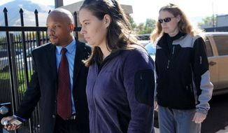 FILE - Jordan Linn Graham, center, leaves the federal courthouse, in this Oct. 4, 2013 file photo taken in Missoula, Mont. The Montana woman who was to be sentenced Thursday for pushing her new husband to his death in Glacier National Park wants to withdraw her guilty plea to a second-degree murder charge, her lawyer said Tuesday March 25, 2014.(AP Photo/The Missoulian, Michael Gallacher, File)