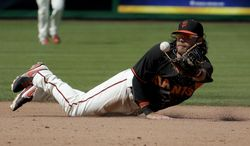 San Francisco Giants shortstop Brandon Crawford throws Colorado Rockies' Ryan Wheeler out at second during the fifth inning of an exhibition baseball game in Scottsdale, Ariz., Wednesday, March 26, 2014. (AP Photo/Chris Carlson)