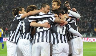 Juventus players hug their teammate Carlos Tevez, hidden at center, after he scored during a Serie A soccer match between Juventus and Parma at the Juventus stadium, in Turin, Italy, Wednesday, March 26, 2014. (AP Photo/Massimo Pinca)