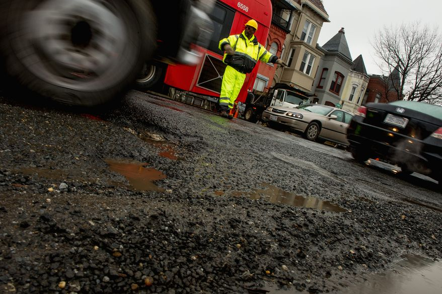 A worker directs traffic through potholes that mark the surface along Florida Ave. in Northwest. (Andrew Harnik/The Washington Times)