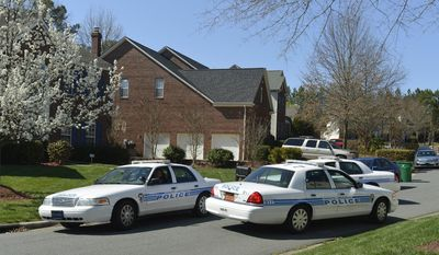 Charlotte-Mecklenburg Police Department cars sit outside Charlotte Mayor Patrick Cannon's home as federal agents search the house, Wednesday, March 26, 2014, in Charlotte, N.C. A city spokesman says Cannon has resigned effective immediately, just hours after he was charged with federal public corruption and bribery. (AP Photo/The Charlotte Observer, Davie Hinshaw) MAGS OUT; TV OUT; NEWSPAPER INTERNET ONLY