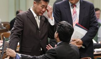** FILE ** This Aug. 16, 2012, file photo shows State Sen. LeLand Yee, D-San Francisco, talking with Assembly members regarding a youth offenders program at the Capitol in Sacramento, Calif. At right is Sen. Juan Vargas, D-San Diego. Yee, the 65-year-old San Francisco Democrat, was arrested Wednesday March 26, 2014, during a series of raids by the FBI in Sacramento and the San Francisco Bay Area. He was later arraigned on charges that alleged illegal dealing in firearms, wire fraud and trading the influence of his office for money. (AP Photo/Rich Pedroncelli, file)