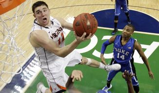 FILE - In this March 16, 2014, file photo, Virginia's Joe Harris (12) goes to the basket against Duke in the second half of an NCAA college basketball game in the championship of the Atlantic Coast Conference tournament in Greensboro, N.C. The ACC is taking its men's basketball tournament from Tobacco Road to the bright lights of New York. A person familiar with the situation said Tuesday, March 25, the league has completed a two-year deal to bring the tournament to Brooklyn's Barclays Center starting in 2017. (AP Photo/Bob Leverone, File)