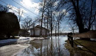 In this March 24, 2014 photo, the Grand River overflows part of its east bank submerging a section of road in front of a home in Grand Rapids, Mich. The river is expected to drop Wednesday before rising again by the middle of next week. (AP Photo/MLive.com, Andrew Kuhn) ALL LOCAL TV OUT; LOCAL TV INTERNET OUT