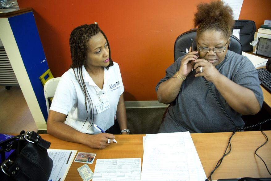** FILE ** In this March 15, 2014, file photo, Alliestean Reese, left, works with Cecila Edwards, with her Affordable Care Act application at a Miami Health Fair. (AP Photo/J Pat Carter, File)