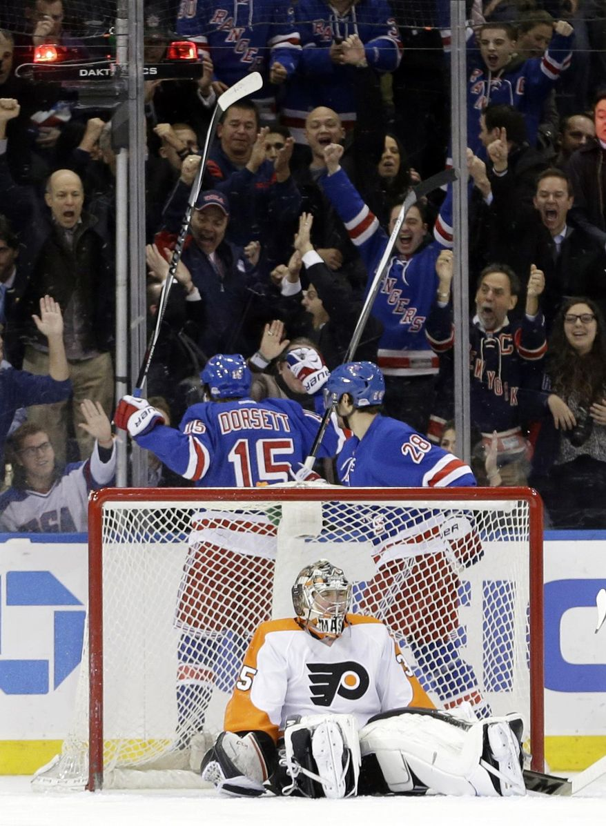 Philadelphia Flyers goalie Steve Mason sits in front of the goal as New York Rangers' Derek Dorsett (15) and Dominic Moore (28) celebrate Dorsett's goal during the first period of an NHL hockey game Wednesday, March 26, 2014, in New York. (AP Photo/Frank Franklin II)