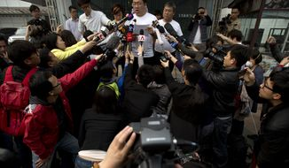 A representative of relatives of Chinese passengers on board Malaysia Airlines Flight 370, center, makes an announcement to journalists prior to a briefing with Malaysian officials at a hotel in Beijing, China, Wednesday, March 26, 2014. About two-thirds of the missing, 239 people on board, are Chinese, and their relatives have lashed out at Malaysia for essentially declaring their family members dead without any physical evidence of the plane's remains. (AP Photo/Alexander F. Yuan)