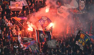 Basel's fans light fireworks  during the Europa League round of 16 second leg soccer match between Red Bull Salzburg and FC Basel in Salzburg, Austria, on Thursday, March 20,  2014. (AP Photo/Kerstin Joensson)