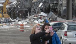 """In this March 25, 2014 photo, Tori Snyder, left, and Marisol Hernandez pose for a """"selfie"""" in front of the Studio 28 movie theater building as demolition begins in Wyoming, Mich. Studio 28 opened in 1965 with one theater and seating for 1,000. It was converted into a multiplex in 1967 with the addition of a second screen, and after several expansions had 20 screens in 1988. It closed in 2008, citing a decline in attendance. (AP Photo/MLive.com, Chris Clark) ALL LOCAL TV OUT; LOCAL TV INTERNET OUT"""