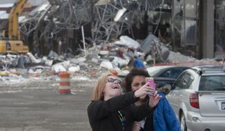 "In this March 25, 2014 photo, Tori Snyder, left, and Marisol Hernandez pose for a ""selfie"" in front of the Studio 28 movie theater building as demolition begins in Wyoming, Mich. Studio 28 opened in 1965 with one theater and seating for 1,000. It was converted into a multiplex in 1967 with the addition of a second screen, and after several expansions had 20 screens in 1988. It closed in 2008, citing a decline in attendance. (AP Photo/MLive.com, Chris Clark) ALL LOCAL TV OUT; LOCAL TV INTERNET OUT"