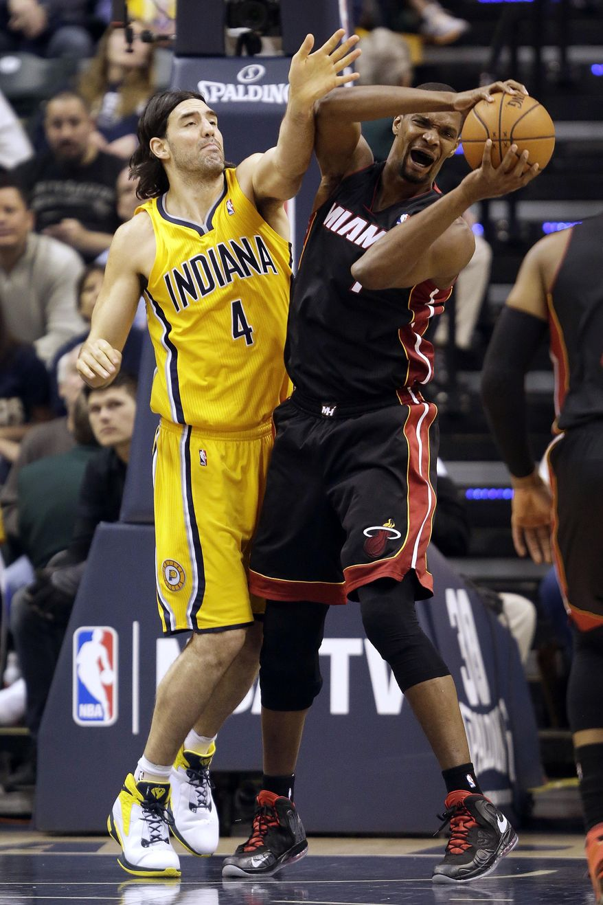 Miami Heat center Chris Bosh, right, pulls in a rebound in front of Indiana Pacers forward Luis Scola, of Argentina, during the first half of an NBA basketball game in Indianapolis, Wednesday, March 26, 2014. (AP Photo/AJ Mast)
