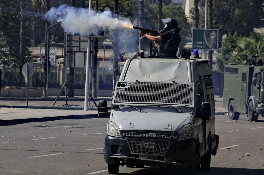 A riot policeman fires tear gas to disperse protesters during clashes outside Cairo University in Giza, Egypt, Wednesday, March 26, 2014. Hundreds of largely Islamist university students in a number of universities protested Wednesday against the mass death sentences issued against more than 520 suspected supporters of President Mohammed Morsi in a cursory trial, setting off clashes that left dozens injured. At Cairo University, hundreds of students who attempted to take their protest outside the campus were met with volleys of tear gas from police. (AP Photo/Ahmed Abd El Latif, El Shorouk) EGYPT OUT