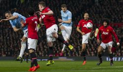 Manchester City's Edin Dzeko, centre, scores his second goal against Manchester United during their English Premier League soccer match at Old Trafford Stadium, Manchester, England, Tuesday March 25, 2014. (AP Photo/Jon Super)