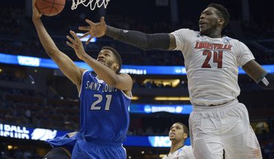 Saint Louis forward Dwayne Evans (21) drives to the basket as Louisville forward Montrezl Harrell (24) defends, during the first half in a third-round game in the NCAA college basketball tournament, Saturday, March 22, 2014, in Orlando, Fla. (AP Photo/Phelan M. Ebenhack)