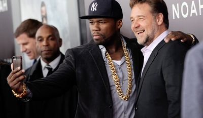 "Rapper and actor Curtis ""50 Cent"" Jackson, left, takes a selfie with actor Russell Crowe at the premiere of ""Noah"" at the Ziegfeld Theatre on Wednesday, March 26, 2014, in New York. (Photo by Evan Agostini/Invision/AP)"