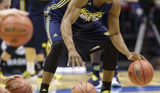 Michigan's Glenn Robinson III dribbles during practice for their NCAA Midwest Regional semifinal college basketball tournament game Thursday, March 27, 2014, in Indianapolis. Michigan plays Tennessee on Friday, March 28, 2013. (AP Photo/Michael Conroy)
