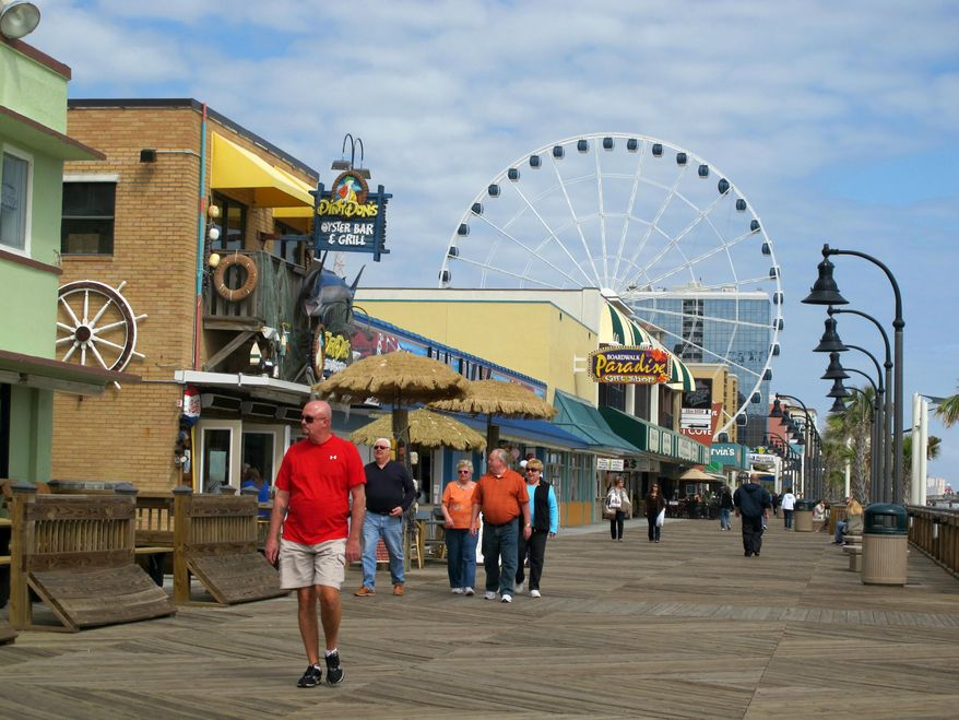 FILE - Visitors walk along the boardwalk in downtown Myrtle Beach, S.C., in this March 7, 2012 file photo. The U.S. Census Bureau announced on Thursday, March 27, 2014 that South Carolina's population is approaching 4.8 million and the Myrtle Beach-Conway-North Myrtle Beach area in South Carolina along with Brunswick County, N.C. is the seventh fastest-growing metropolitan area in the nation. (AP Photo/Bruce Smith, file).