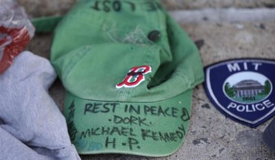 A baseball cap with a written tribute to fallen Boston firefighter Michael Kennedy rests at a makeshift memorial in front of fire station Engine 33, Thursday, March 27, 2014, in Boston. Fire station Engine 33 was the station of fallen firefighters Kennedy and Lt. Edward Walsh and who lost their lives fighting a 9-alarm fire in a four-story brownstone in Boston's Back Bay neighborhood Wednesday, March 26, 2014. (AP Photo/Steven Senne)