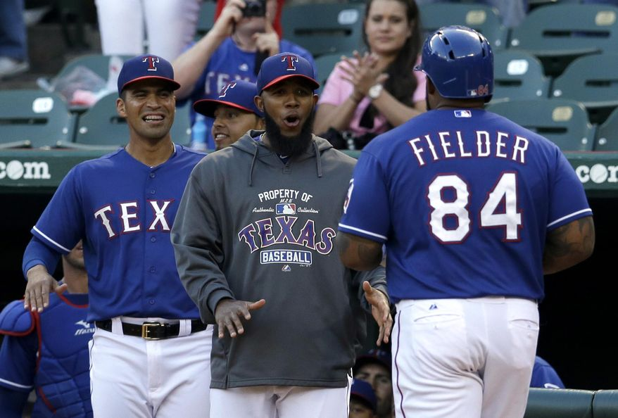 Texas Rangers' Robinson Chirinos, left, and Elvis Andrus, center, celebrate as they greet teammate Prince Fielder (84) at home home following Fielder's 2-run home run that came off a throw by Quintana Roo Tigres starting pitcher Amaury Sanit in the first inning of a spring exhibition baseball game onThursday, March 27, 2014, in Arlington, Texas. (AP Photo/Tony Gutierrez)