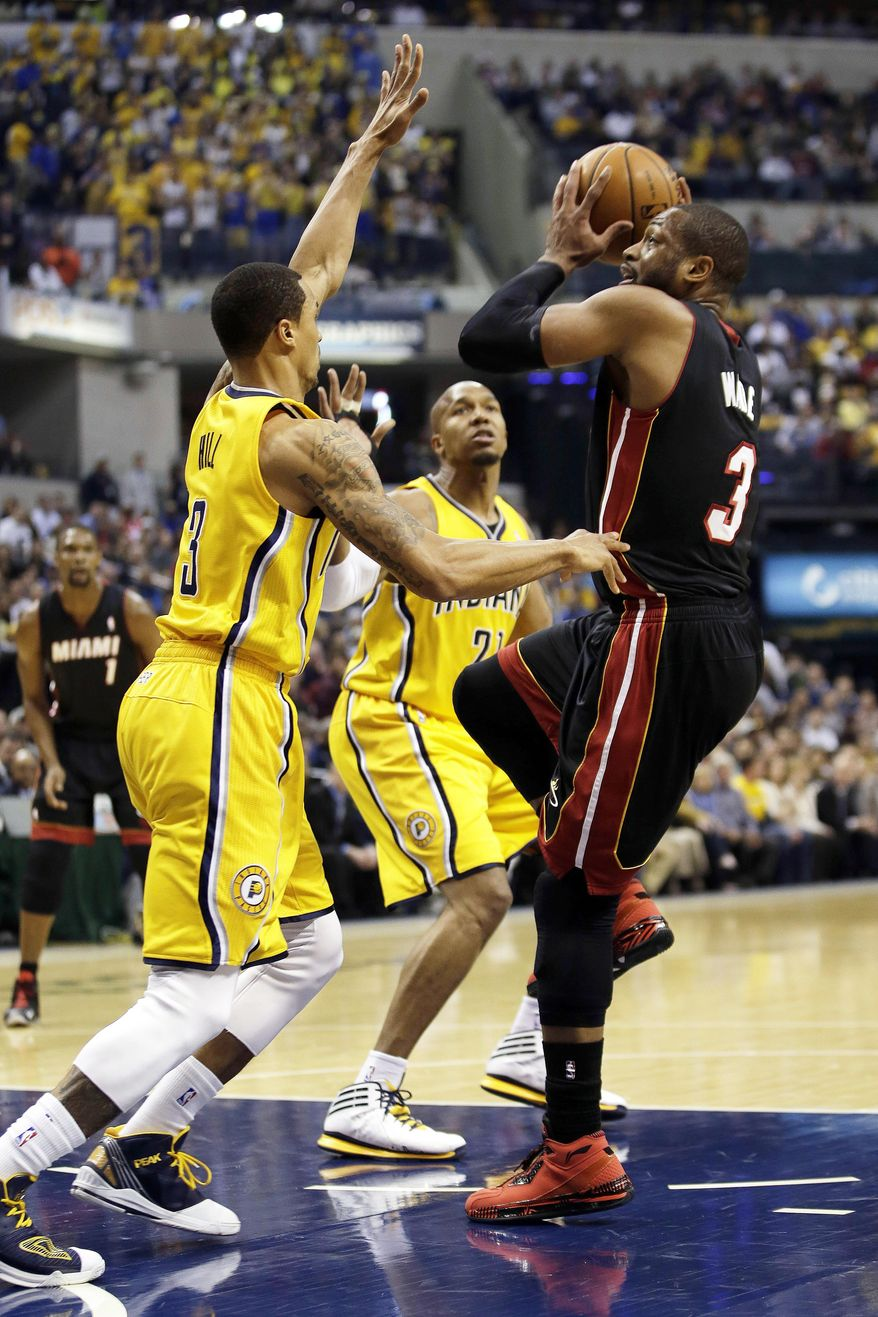 Miami Heat guard Dwyane Wade, right, shoots over Indiana Pacers guard George Hill during the first half of an NBA basketball game in Indianapolis, Wednesday, March 26, 2014. The Pacers won 84-83. (AP Photo/AJ Mast)