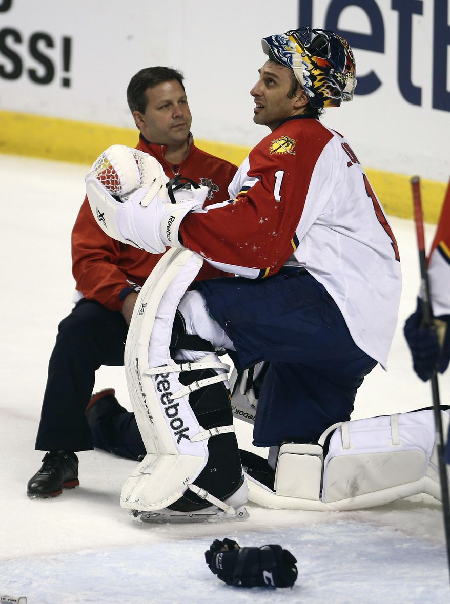 Florida Panthers head athletic trainer Dave Zenobi, left, checks goalie Roberto Luongo (1) after Carolina Hurricanes' Radek Dvorak slammed into him during the first period of an NHL hockey game in Sunrise, Fla., Thursday, March 27, 2014. (AP Photo/J Pat Carter)