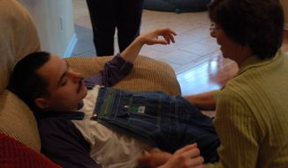 ADVANCE FOR WEEKEND EDITIONS, MARCH 29-30 - In this photo taken on Monday, March 17, 2014, Nancy Gardenhire, right, slides her son, LJ off the couch at their home in Sumter, S.C. He has cerebral palsy. (AP Photo/The Item, Jade Reynolds)