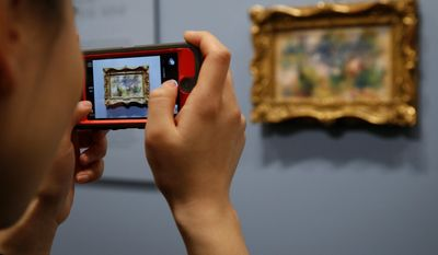 "A woman photographs Pierre-Auguste Renoir's painting ""On the Shore of the Seine"" after a news conference at the Baltimore Museum of Art in Baltimore, Thursday, March 27, 2014, more than 60 years after it was stolen from the museum. The painting became the subject of a dramatic legal dispute after a Virginia woman claimed she bought it at a flea market for $7. A judge ultimately awarded ownership back to the Baltimore museum, and it is scheduled to go on public display March 30. (AP Photo/Patrick Semansky)"