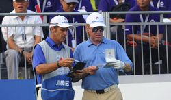 Spain's Miguel Angel Jimenez, right, listens to his caddy before teeing off on the first hole during the first round of the Eurasia Cup golf tournament at the Glenmarie Golf and Country Club in Subang, Malaysia, Thursday, March 27, 2014. (AP Photo/Joshua Paul)