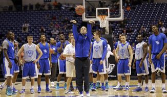 Kentucky head coach John Calipari shoots a half court shot as players watch during practice for their NCAA Midwest Regional semifinal college basketball tournament game Thursday, March 27, 2014, in Indianapolis. Kentucky plays Louisville on Friday, March 28, 2013. (AP Photo/David J. Phillip)
