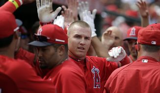 Los Angeles Angels's Mike Trout is congratulated after scoring during an exhibition spring training baseball game against the Chicago White Sox Thursday, March 13, 2014, in Tempe, Ariz. (AP Photo/Morry Gash)