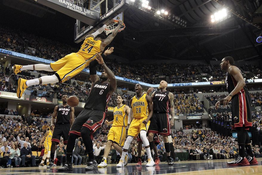 Indiana Pacers forward Paul George (24) hangs on the rim after dunking in front of Miami Heat forward LeBron James (6) during the second half of an NBA basketball game in Indianapolis, Wednesday, March 26, 2014. The Pacers won 84-83. (AP Photo/AJ Mast)