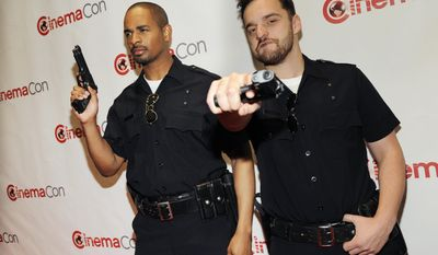 "Jake Johnson, right, and Damon Wayans Jr., cast members in the upcoming film ""Let's Be Cops,"" pose together before the 20th Century Fox presentation at CinemaCon 2014 on Thursday, March 27, 2014, in Las Vegas. (Photo by Chris Pizzello/Invision/AP)"