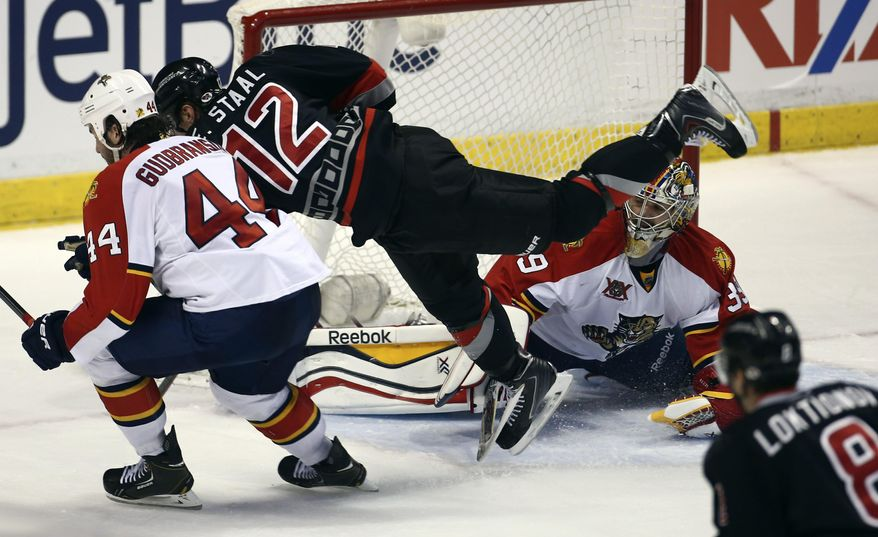 After taking a shot on goal, Carolina Hurricanes' Eric Staal (12) dives past Florida Panthers' goalie Dan Ellis (39) and Erik Gudbranson (44) during the second period of an NHL hockey game in Sunrise, Fla., Thursday, March 27, 2014. (AP Photo/J Pat Carter)