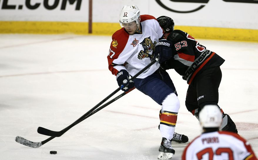Florida Panthers' Jesse Winchester (17) and Carolina Hurricanes' Jeff Skinner (53) battle for the puck during the second period of an NHL hockey game in Sunrise, Fla., Thursday, March 27, 2014. (AP Photo/J Pat Carter)